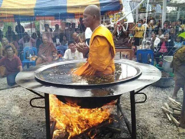 Thai monk meditates in boiling oil pot over a campfire